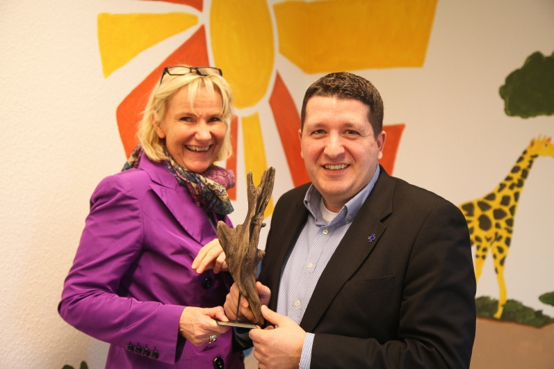 """Petra Niederau (Head of HR) und Marcel Rütten (HR Manager) von der Kindernothilfe mit der Auszeichnung """"A.T. Kearney Family Award"""" als familienfreundlichste Organisation Deutschlands."""